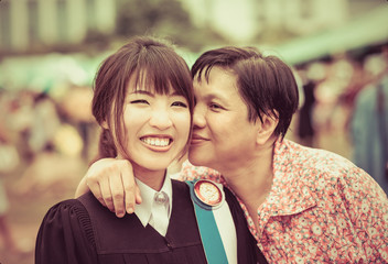 Mother is kissing her daughter with joy for her master degree gr