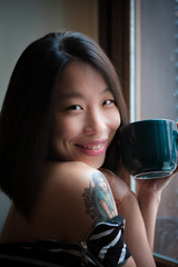 Asian cute woman smiles with green mug
