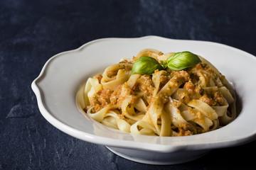 Traditional Italian fettuccine pasta with red Sicilian pesto