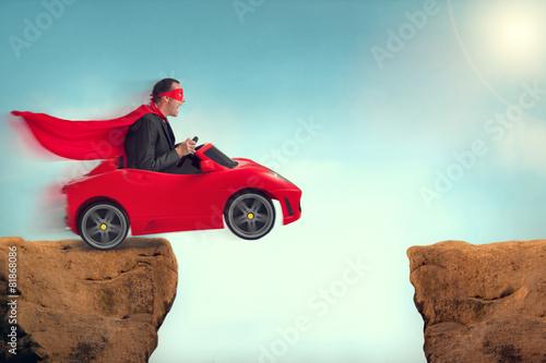 Leinwanddruck Bild man in a car jumping a ravine