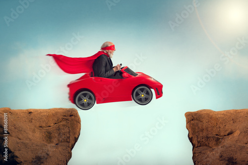 senior superhero driving a car off a ravine