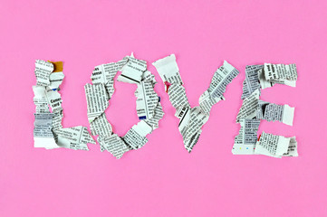 Word love made of newspaper pieces on bright pink background.