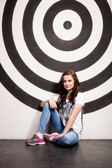 slim woman sitting on floor against wall with big painted target