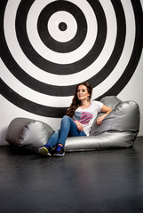Sexy young woman posing on big soft chair in studio