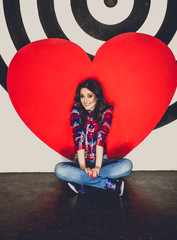 Toned photo of woman posing at studio with big red heart