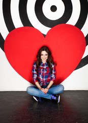 Young smiling woman sitting on floor with big red heart