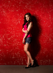 Sexy slim woman with curly black hair leaning against red wall