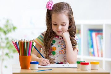 Cute little preschooler child drawing at home