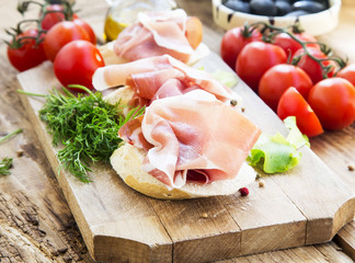 Prosciutto Ham Appetizer with Spices on a Wooden Cutting Board