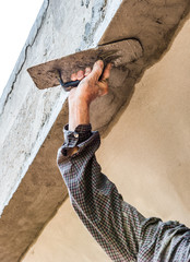 Worker plastering ceiling and wall