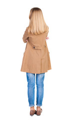 back view of standing young beautiful  blonde woman in brown clo