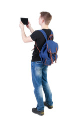 Back view of standing young man with tablet computer and backpac