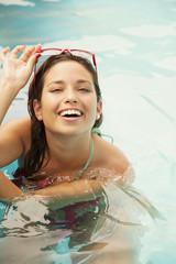 Happy young woman having fun in swimming pool