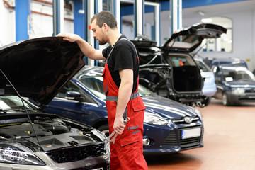 KFZ Mechaniker repariert Fahrzeug in einer Autowerkstatt