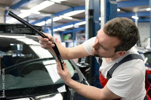 Leinwanddruck Bild KFZ Mechaniker kontrolliert die Wischerblätter am Auto
