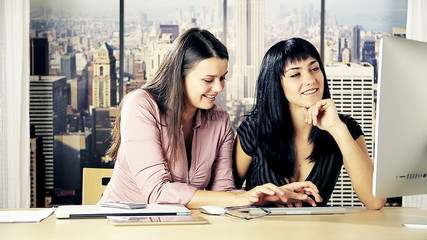 Women at work chatting on computer laughing flirting