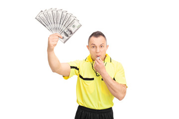 Furious referee blowing a whistle and holding money