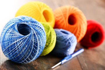 Colorful yarn for crocheting and hook on wooden table