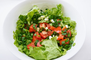 Healthy green salad, in white bowl.
