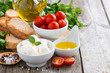 delicious mozzarella and ingredients for a salad on wooden table