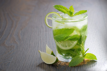 mojito cocktail and ingredients on a wooden table