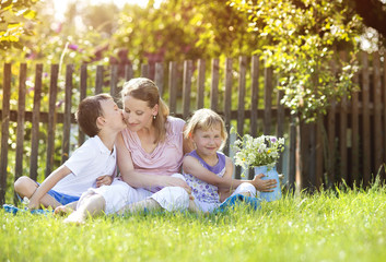 Happy mother with her children spending time together outside