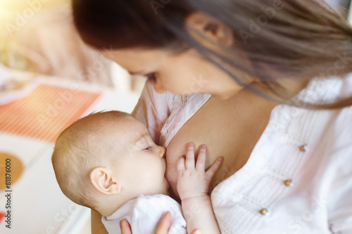 Mother breastfeeding her little baby girl in her arms - 81876000