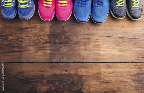 Various running shoes laid on a wooden floor background - 81876033