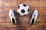 Fototapety Football boots and ball laid on a wooden floor background
