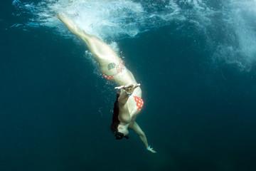 beautiful girl swimming under a ship