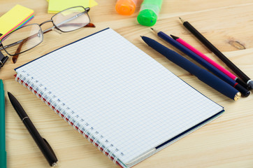Overhead of open notebook with pen and glasses on a desk