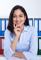 Türkische Geschäftsfrau im Büro lacht in die Kamera
