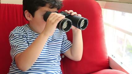 Child looking through binoculars and smiling