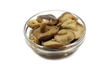 marinated mushrooms in a glass on a white background