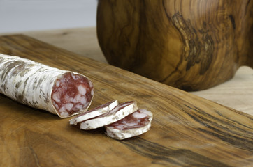 SSpanish fuet salami over rustic wooden cutting board.