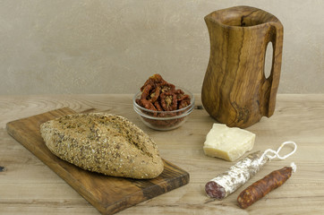 Spanish fuet, chorizo, olive wooden cutting board and pitcher.