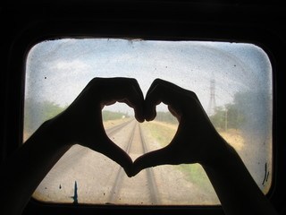 Silhouette Of Hands Making Heart On Dirty Train Window