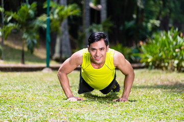 Strong Asian man doing sport push-up in park