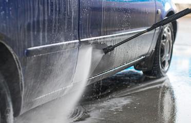 Blue car wash using high pressure water jet.