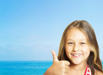 pretty laughing little girl shows his thumb on sea background