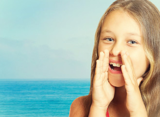girl speaks through cupped hands on sea background