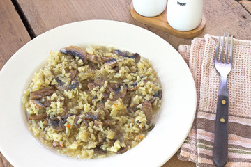 Risotto with mushrooms on plate with fork