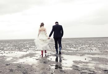 Brautpaar geht im Watt spazieren