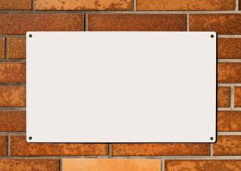 Ein leeres weisses Schild auf einer orange verklinkerten Wand