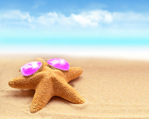 Summer beach. Starfish in pink sunglasses on the seashore.
