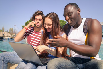 Multiracial friends having fun with laptop and smartphone