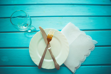 Knife, fork and dish over wooden table