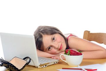 a little girl sitting at his desk with a bowl of strawberries