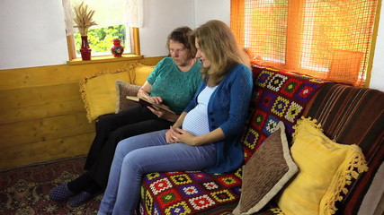 Pregnant granddaughter woman with grandma read book