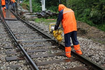 Worker repairs railroad on rainy day with machine